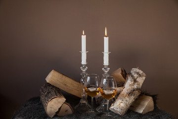 Two candles with two glasses of wine surrounded by wood