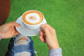 Woman hands holding hot cups of coffee with milk foam on green background with copy space