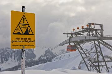 Hinweisschild am Pistenrand, Alpen, Seilbahn im Hintergrund