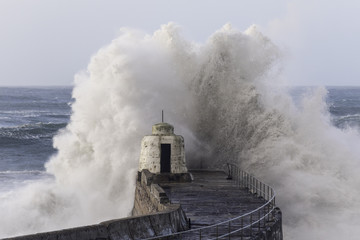 Huge wave breaks above the Pepper Pot on Portreath harbour wall