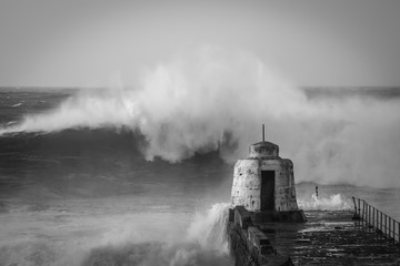 Large wave breaks off Portreath harbor wall - black and white