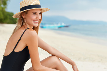 Pretty female sits on sandy beach, dressed in swimsuit and summer hat, looks at ocean panorama, being in good mood, relaxes during hot tropical day at exotic country. White sand and crystal blue sea