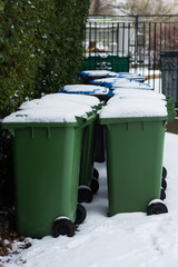 row of wheelie bins in the UK with snow on top awaiting collection
