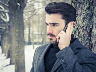 Handsome trendy man wearing black jacket standing and talking on cell phone, outdoor in city setting in winter day shot