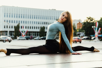 Ballerina sitting in gymnastic pose in middle of city street. buildings background.