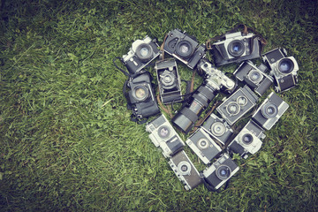 Heart shape made by collection of old vintage retro SLR film cameras, lying on green grass lawn background.