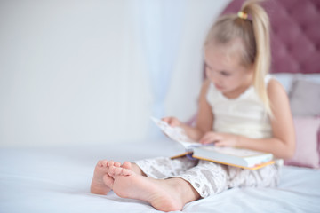 Little blonde girl sitting on the bed reading a book with focus on the feet indoors