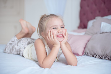 Cute pretty little girl with a beaming smile lying on her stomach a bed looking up into the air with a happy expression as she watches something.