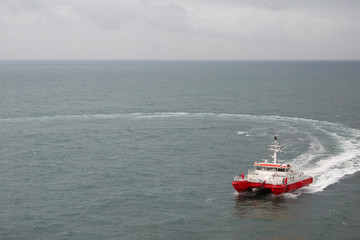Modern tugboat of red and white color in the sea