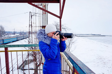 The girl photographs in the winter in a dark blue jacket on a dlinnofokusny lens on the bridge near the frozen sea on the railway.