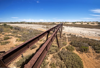 Australia – Old Ghan railway bridge over a dried-out river bed at the outback desert under blue sky