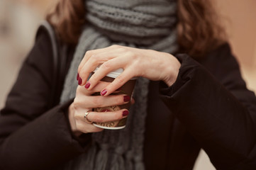 Young girl in warm scarf on the street holding coffee to go or take away while walking in the park, mock-up of coffee cup