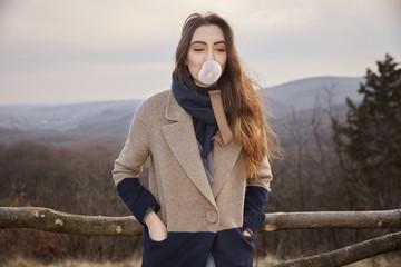 one young cute Caucasian girl, looking away, blowing bubble gum, wearing winter autumn coat, scarf.