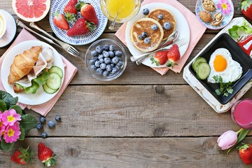 Breakfast food table. Festive brunch set, meal variety with fried egg, pancakes, croissants, smoothie ,fresh berries and fruits. Overhead view