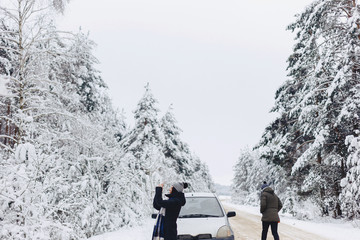 girl in winter clothes on snowy forest road picks up landscapes