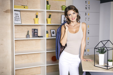 Beautiful rich caucasian business woman standing in her modern office in casual outfit. Neutral interior with book shelves. Woman smiles friendly