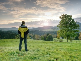 Photographer on autumnal meadow is waiting for sunrise.