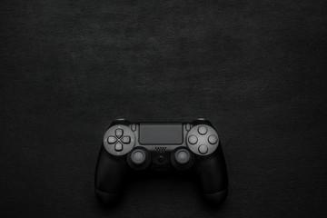 Black gamepad on a dark wooden background