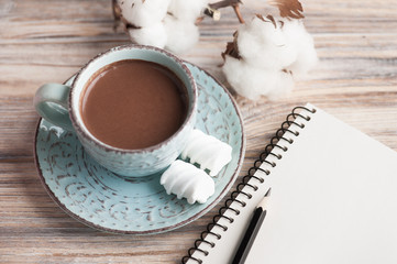 Cup of hot chocolate and notebook