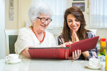 Cheerful grandmother and granddaughter looking at family photo album at home.