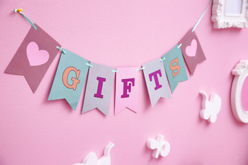 Handmade garland with word GIFTS on color wall