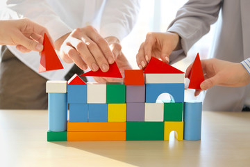 People building house together on table, closeup. Unity concept