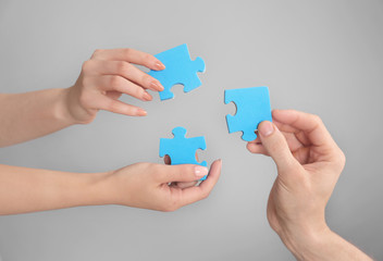 People holding puzzle pieces together on grey background. Unity concept