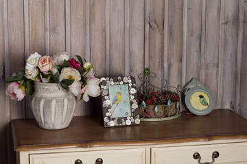 flowers in a vase with a frame on the dresser