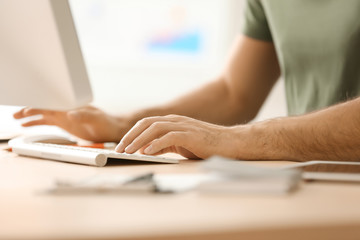 Man working with computer at table in office, closeup