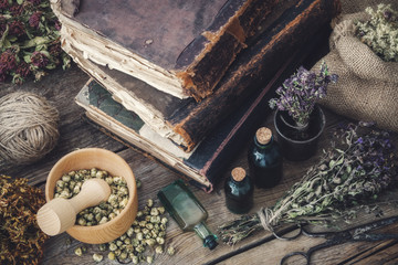 Tincture bottles, assortment of dry healthy herbs, old books, mortar, scissors on old wooden desk. Herbal medicine. Top view.