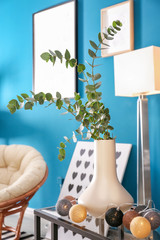 Vase with twigs and electric garland on table in living room