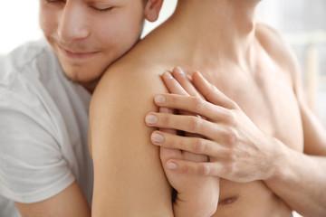 Young gay couple hugging, closeup view