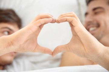 Young gay couple making heart symbol with their hands while lying in bed