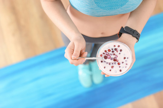 Sporty young woman eating yogurt with berries after fitness training at home