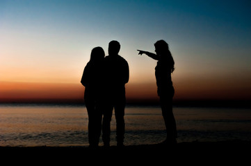 Silhouette of three friends in the morning at the beach looking at sunrise .