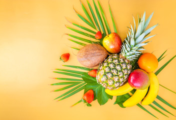 Flat lay of various tropical fruits on palm leaves. Pineapple, mango, banans, orange, apple and strawberries. Golden background. Square.