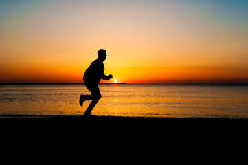 Silhouette of runner old man in the morning at the beach, sunrise Background.