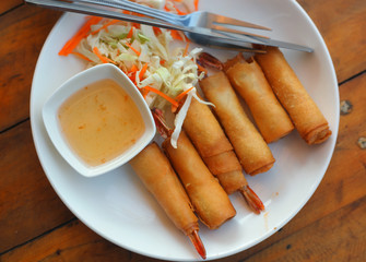 top view photo of roasted spring rolls with shrimps sore and sweet sauce