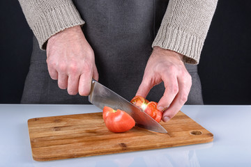The man cut a tomato into two halves with a knife. A beautiful photo of the cooking process.