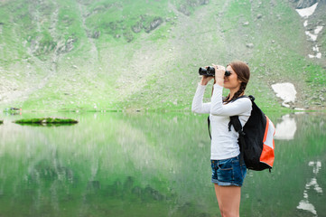 Young woman admiring the beautiful view of the lake and mountains, holding a binocular. Scene from Balea Lake, Romania.