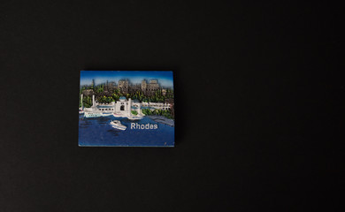 Souvenir - Fridge magnet from Rhodes, Greece on black background