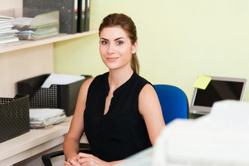 Closeup of young beautiful young business woman smiling at office