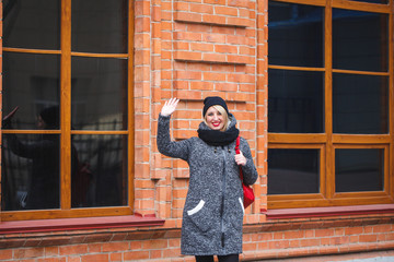 A young modern girl with a raised hand waving and welcoming in the open air. Portrait of a hipster girl, who greets. Gesture of greeting.