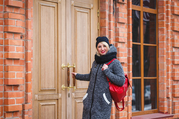 A modern young girl in a coat and hat opens the door and looks at the camera in the open air. Female student opens the door to the building and looks at the camera and smiles