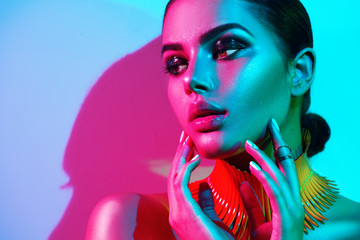Wall Mural - Fashion model woman in colorful bright lights with trendy makeup and manicure posing in studio