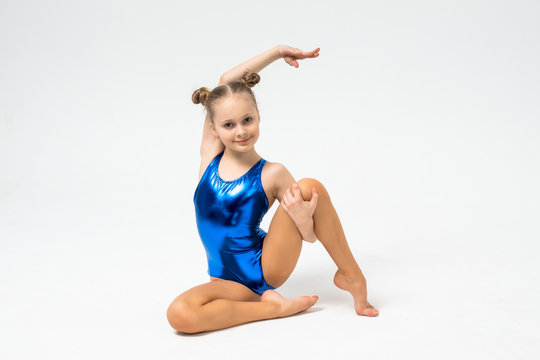 A young teenage girl in leotard shows gymnastic and ballet exercises on a white background.