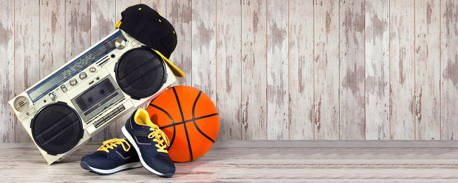 The concept of the music Hip hop style and sports .Vintage audio player ,fashionable cap, sneakers and basketball ball.
