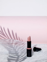 Single nude lipstick isolated on white and pink background. Copy space.