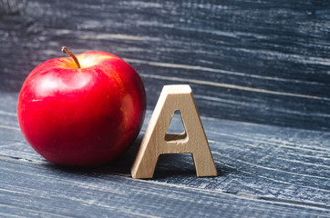 Red apple and letter A. The concept of primary education. Apple for the teacher. Sadik, school, college, university, educational institution. Alphabet alphabet. Score A.