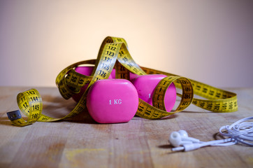 Concepts for Fitness, still life with pink weights, earphones and a yellow tape measure